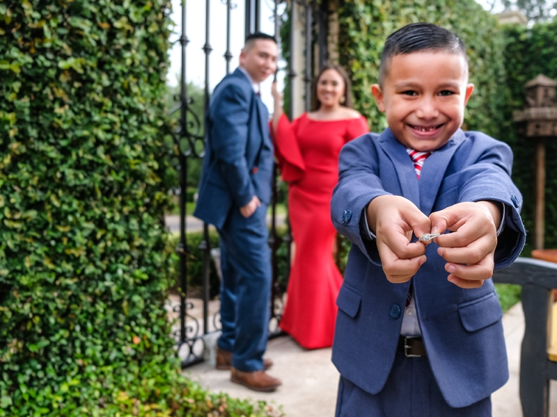 With a big smile on his face, a boy outstretches his hands to the camera holding onto the engagement ring of his parents. In the background you can see the smiling faces of his parent and their fiance. They are surrounded by the lush greenery from the Casa Polonia in Weslaco Texas.